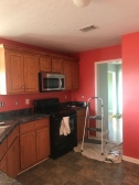 The original kitchen. Red walls, blue-gray laminate, and yellow oak cabinets. Ew.